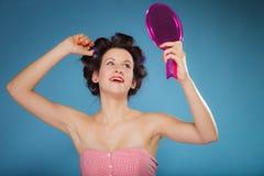 Волосы дизайна девушки при curlers смотря в зеркале Стоковое Изображение