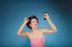 Волосы дизайна девушки при curlers смотря в зеркале Стоковые Фото