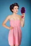 Волосы дизайна девушки при curlers смотря в зеркале Стоковые Изображения