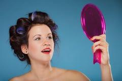 Волосы дизайна девушки при curlers смотря в зеркале Стоковые Фотографии RF