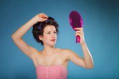 Волосы дизайна девушки при curlers смотря в зеркале Стоковая Фотография