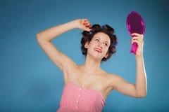 Волосы дизайна девушки при curlers смотря в зеркале Стоковые Изображения RF