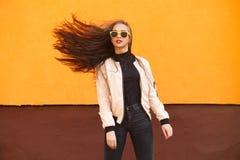 Волосы красивого iwith девушки битника fluing в желтых солнечных очках на оранжевой стене напольно Экземпляр-космос Стоковое Изображение