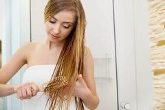 волосы Красивое белокурое чистящ ее влажные волосы щеткой Внимательность волос Щеголь курорта Стоковые Изображения