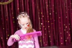 Волосы клоуна маленькой девочки чистя щеткой с большим гребнем Стоковые Изображения