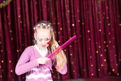 Волосы клоуна маленькой девочки чистя щеткой с большим гребнем Стоковое Изображение