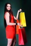 Молодая женщина с бумажной multi покрашенной хозяйственной сумкой Стоковое Изображение