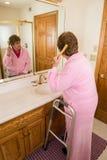 Волосы пожилой старшей женщины чистя щеткой стоковые изображения