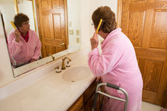Волосы пожилой старшей женщины чистя щеткой стоковая фотография rf