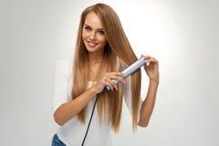 волосы прямо Красивая женщина утюжа длинные белокурые волосы Стоковое фото RF