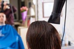 Волосы стилизатора суша женского клиента в салоне Стоковое Изображение RF