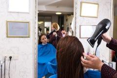 Волосы стилизатора суша женского клиента в салоне Стоковые Фотографии RF