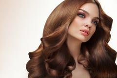 волос девушки предпосылки пинк красивейших коричневых курчавых здоровый изолированный женщина портрета красивейших волос длинняя  Стоковая Фотография