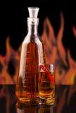 Водочка бутылки и стекла с перцем chili на пламенах предпосылки Стоковая Фотография RF