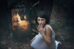 Волшебное зеркало и удивленная женщина в темном лесе Стоковое фото RF