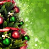 Волшебно украшенная ель с шариками, лентами и гирляндами на запачканной Рождеств-зеленой сияющей и сверкная предпосылке Стоковые Изображения