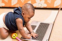 Вползая младенец играя с клавиатурой компьтер-книжки стоковое фото rf