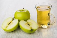 Вполне и половины зеленых яблок, чашки яблочного сока Стоковые Фото