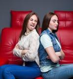 2 враждуя девушки сидят на красном кожаном кресле Стоковая Фотография
