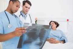 Врачует рассматривая рентгеновский снимок пациентом в больнице Стоковое Изображение