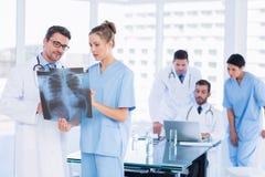 Врачует рассматривая рентгеновский снимок при коллеги используя компьтер-книжку позади Стоковое Фото