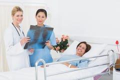 Врачует рассматривая рентгеновский снимок с пациентом в больнице Стоковая Фотография RF