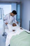 Врачуйте взаимодействовать при пациент лежа на непредвиденном растяжителе стоковые изображения