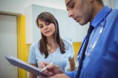 Врачуйте взаимодействовать с пациентом и запись на доске сзажимом для бумаги стоковые изображения rf