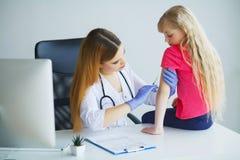 Врачуйте впрыскивать вакцинирование в девушке маленького ребенка руки, здоровое стоковое изображение