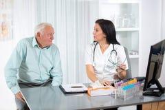 Врачуйте говорить к ее мужскому старшему пациенту на офисе стоковое изображение rf