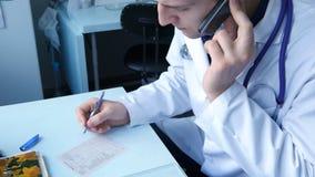 Врачуйте говорить на телефоне и запись медицинского рецепта в больнице Стоковая Фотография RF