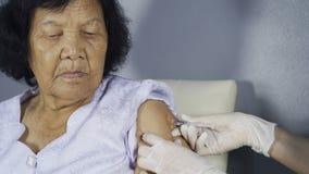 Врачуйте давать вакционную впрыску в старшую женщину сток-видео