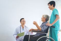 Врачуйте держать пожилую терпеливую руку ` s в wheelchai, давая su стоковая фотография rf