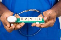Врачуйте держать стетоскоп и шильдик при надпись здоровья изолированная на светлой предпосылке стоковое фото