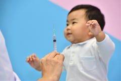 Врачуйте держать шприц с вакциной для азиатского младенца Стоковые Фотографии RF