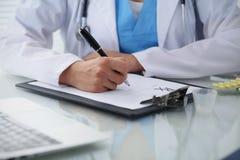 Врачуйте женщину заполняя вверх по рецепту, концу-вверх рук Врач на работе Концепция медицины и здравоохранения Стоковые Изображения RF