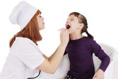 Врачуйте женщину проверяя горло молодой терпеливой девушки Стоковые Изображения RF