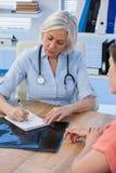 Врачуйте запись рецепта для ее пациента в медицинском офисе Стоковые Фотографии RF