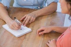 Врачуйте запись рецепта для ее пациента в медицинском офисе Стоковая Фотография