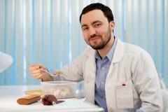 Врачуйте иметь обед на его офисе во время пролома Работник есть гречиху от пластмасового контейнера коробки для завтрака Стоковое Фото