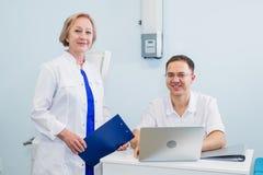 Врачуйте иметь переговор с его коллегой и держать рентгеновский снимок в медицинском офисе стоковое фото