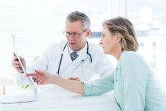 Врачуйте иметь переговор с его пациентом и держать рентгеновский снимок стоковое фото
