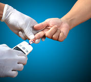 Врачуйте испытывать уровень глюкозы пациентов после колоть его finge стоковое изображение