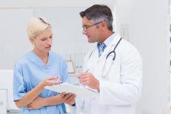 Врачуйте и вынянчите обсуждать над примечаниями в клинике стоковое изображение