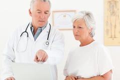 Врачуйте и его пациент смотря компьтер-книжку Стоковые Изображения RF