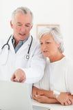 Врачуйте и его пациент смотря компьтер-книжку Стоковая Фотография