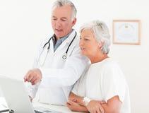 Врачуйте и его пациент смотря компьтер-книжку Стоковые Фото