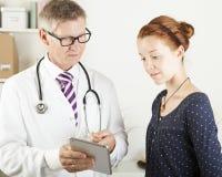 Врачуйте и терпеливая женщина смотря что-то на ПК таблетки Стоковая Фотография