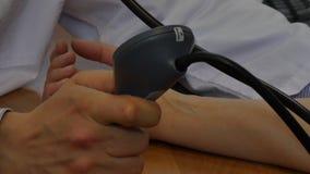 Врачуйте кровяное давление измерений артериальное пациента tonometer в клинике сток-видео