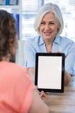Врачуйте обсуждать с пациентом над цифровой таблеткой на больнице Стоковое фото RF